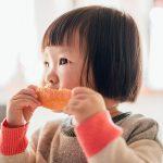 baby girl eating orange